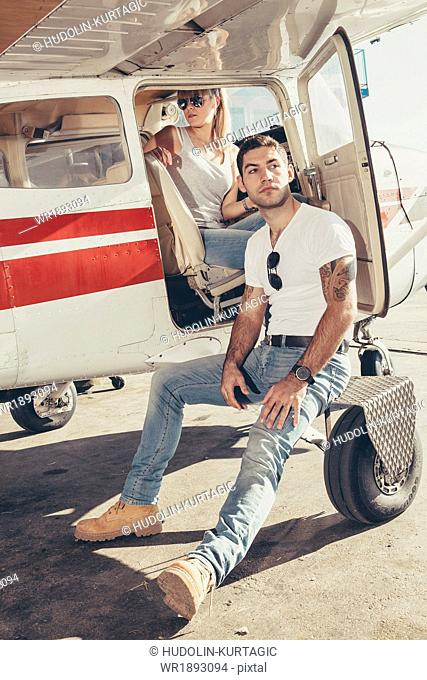 Young couple preparing for start in propeller airplane