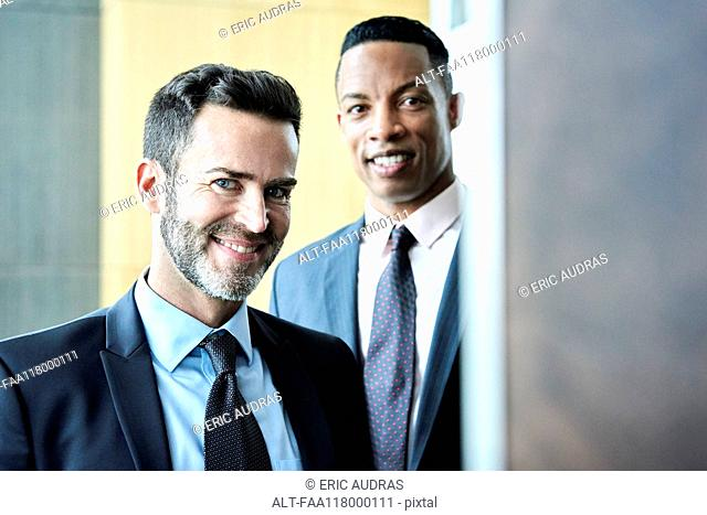 Smiling businessmen standing in hotel lobby