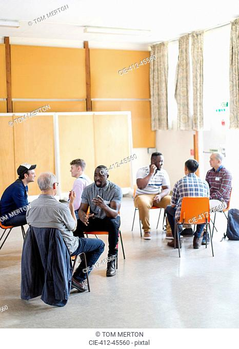 Men talking in group therapy in community center