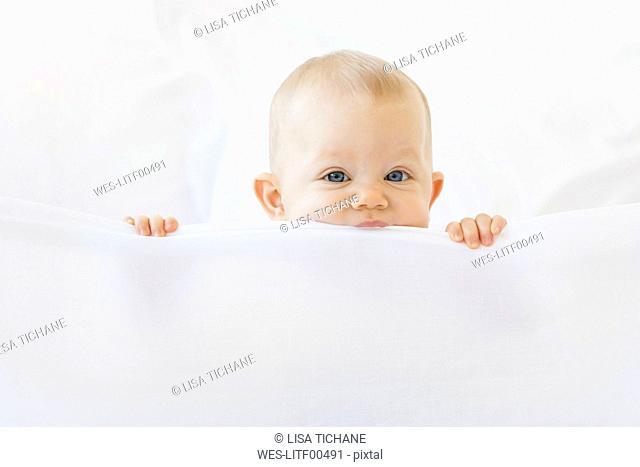 Baby girl peeking over white bed sheet