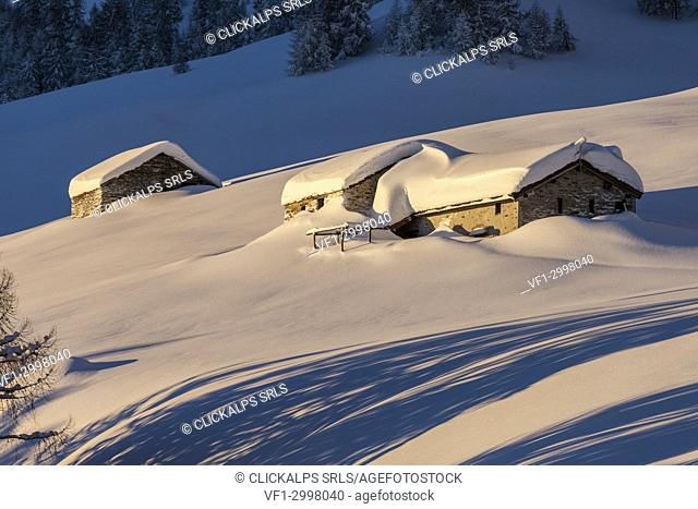 Stone huts covered with snow, Monte Olano, Gerola Valley, Sondrio province, Valtellina, Lombardy, Italy