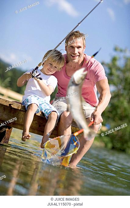Father and young boy on jetty fishing