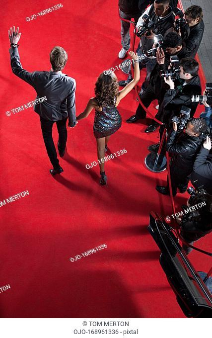 Celebrities waving to paparazzi on red carpet