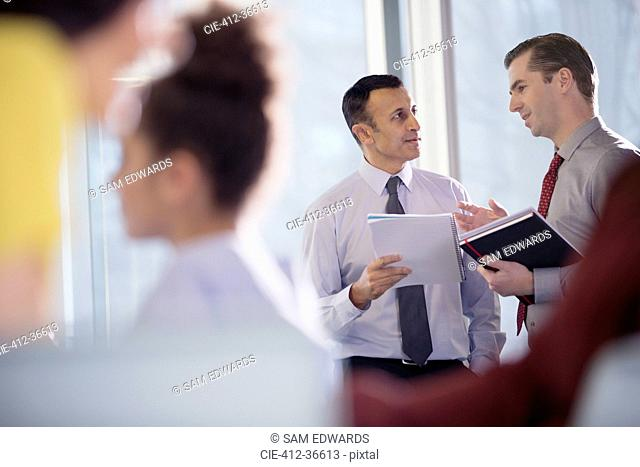 Businessmen talking in office window