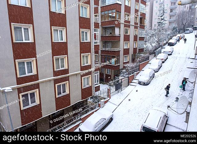 people walking around in a neighborhood while snow falling continuously in winter time