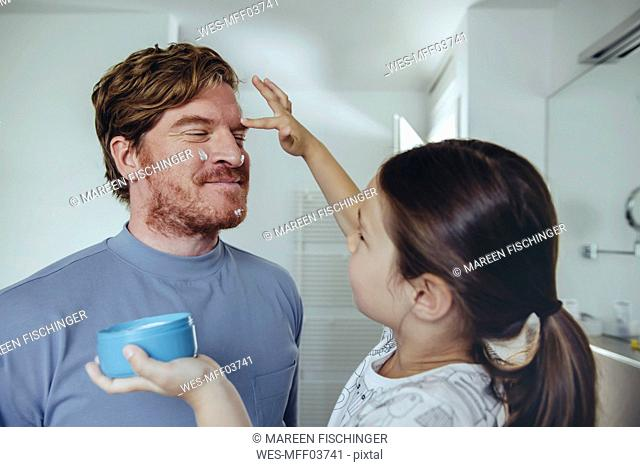 Daughter putting facial cream on father's face