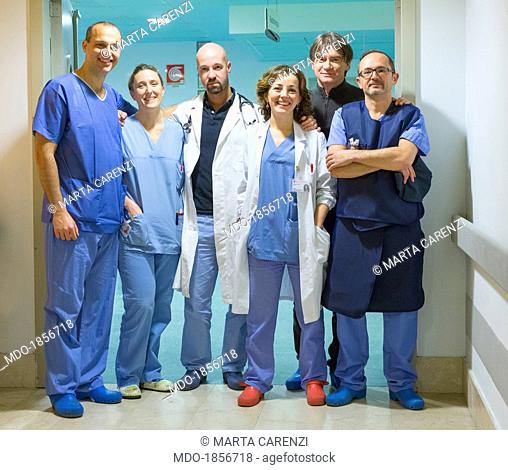 Medical Staff in white and blue coats posing inside a hospital ward. San Donato (Italy), January 2014