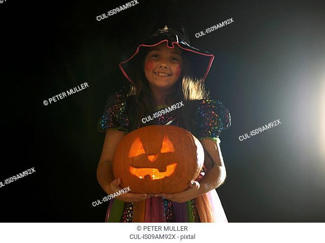 Portrait of girl wearing halloween witch costume holding pumpkin