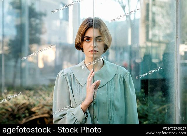 Portrait of woman with her face resting on a glass pane