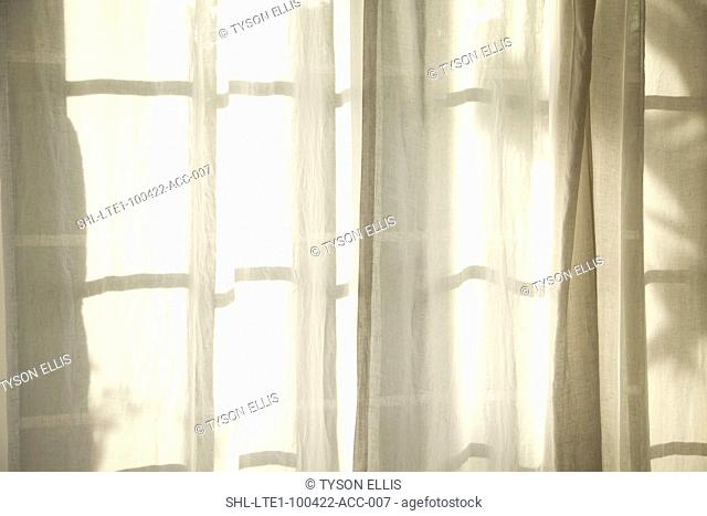 White fabric curtains in front of window