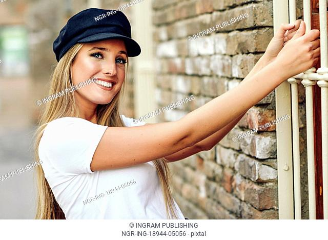 Young blonde woman smiling near a brick wall. Girl with blue eyes wearing white t-shirt and cap