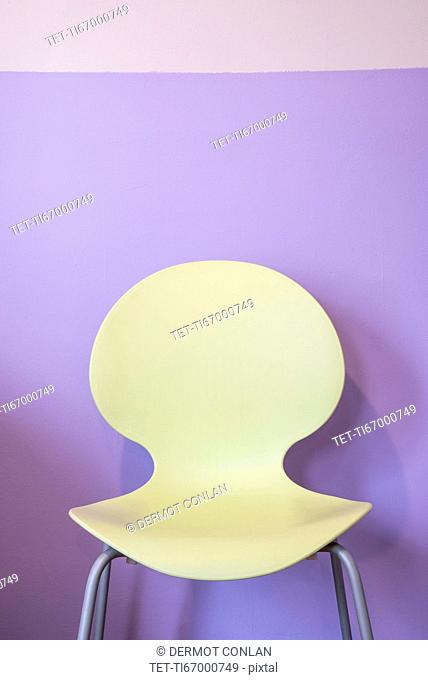 Empty yellow chair by purple wall