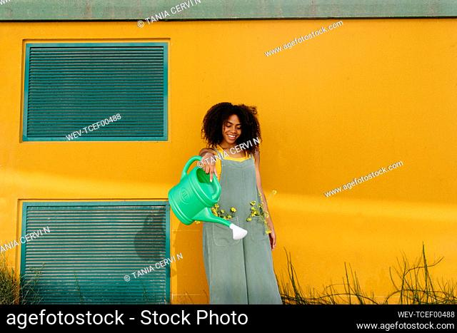 Young woman wearing overalls watering flowers in front of yellow wall