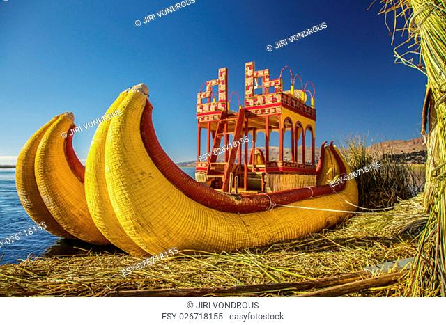 Reed boat on Island of Uros. Those are floating islands on lake Titicaca located between Peru and Bolivia. Colorful image with yellow boat and clear blue sky
