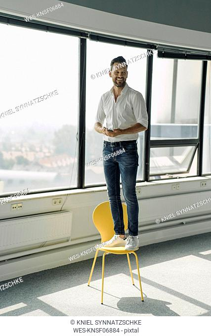 Happy mature businessman standing on yellow chair in empty office