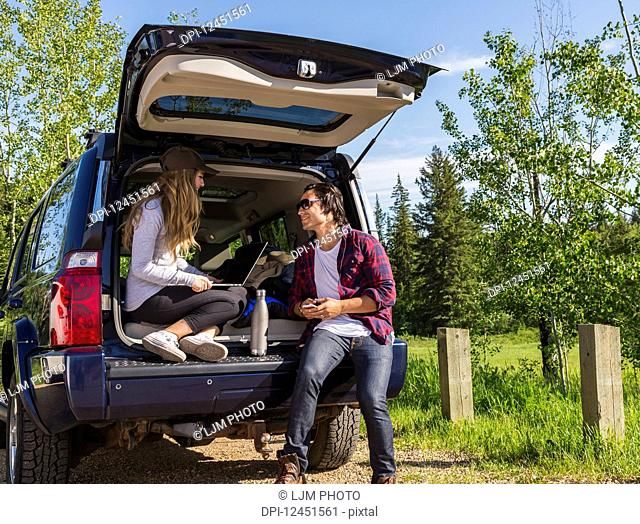 Young couple at their vehicle with the back open looking at a laptop computer; Edmonton, Alberta, Canada