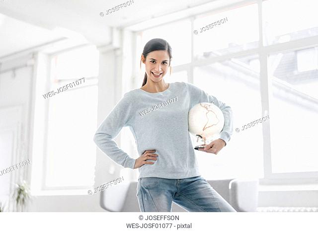 Young woman holding globe, planning world trip
