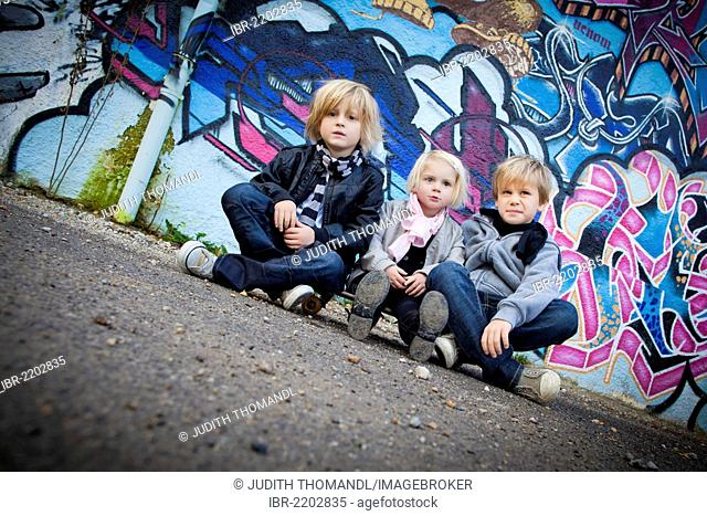 Siblings, 2, 5 and 7 years, sitting on a skateboard in front of a wall with graffiti