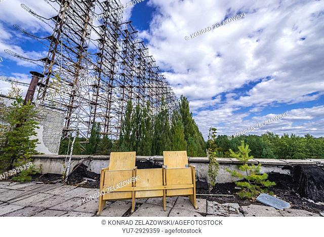 Chairs on roof in Chernobyl-2 military base in Chernobyl Nuclear Power Plant Zone of Alienation, Ukraine. Old Sovier radar called Duga on background