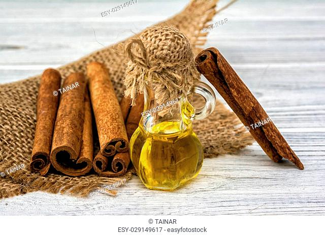 Essential cinnamon oil in bottle and cinnamon cticks on sackcloth