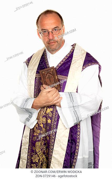 ein katholischer Priester mit Bibel im Gottesdienst