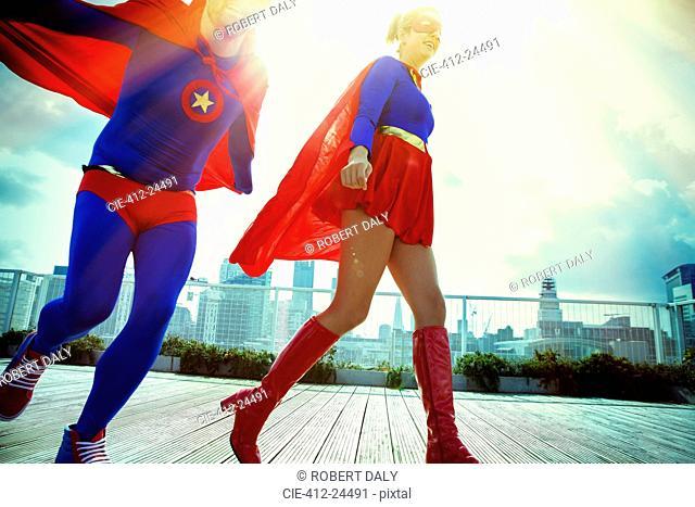 Superheroes running on city rooftop