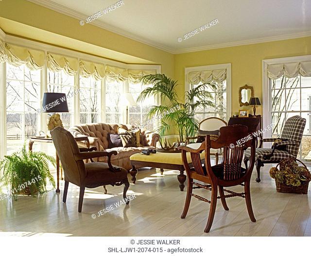LIVING ROOM: Sunny yellow sitting area, light maple wood floors, windows extendto the floor, balloon valances, bay window, tufted chesterfield style sofa