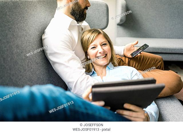 Smiling woman with tablet and man with cell phone on couch