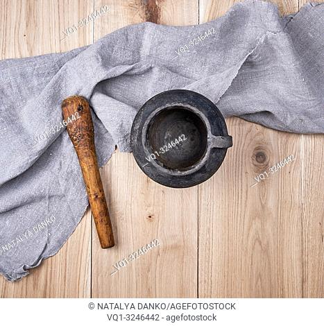 empty old black ceramic pot on wooden background, top view