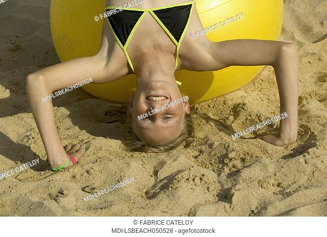 Young girl playing with a big yellow balloon on the sand beach