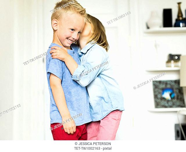 Little girl (4-5) whispering into brother's (4-5) ear