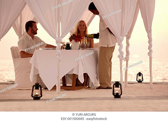 Portrait of an attractive honeymoon couple enjoying romantic candlelight dinner by the sea