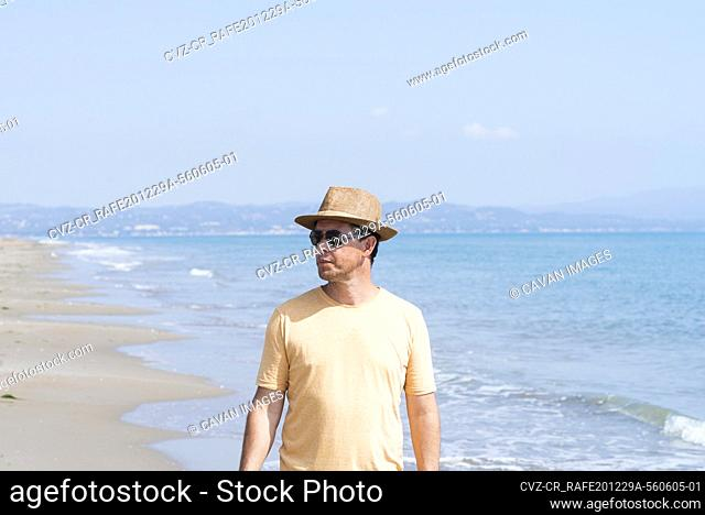 Man with hat and sunglasses standing on seashore, while looking away