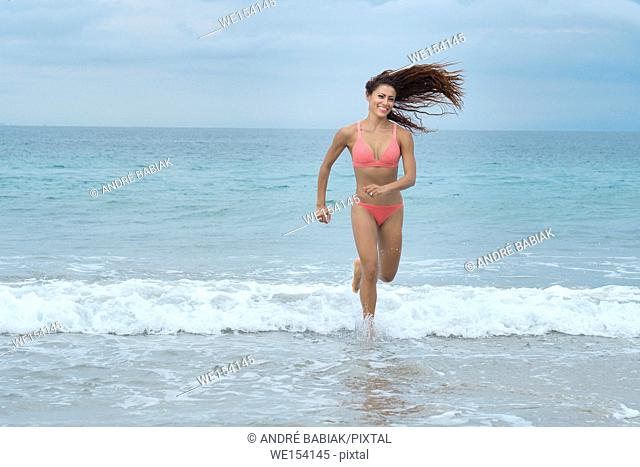 Attractive woman in bikini running at a beach