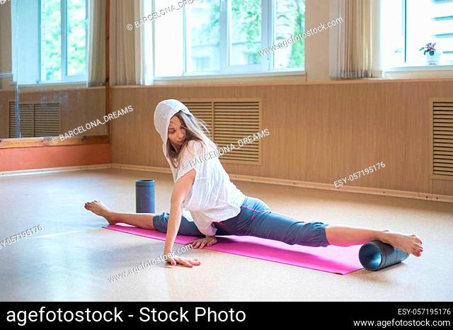 Young slim woman with blonde hair sitting on the yoga mat in split - using auxiliary stand under the foot - stretching one leg. Mid shot