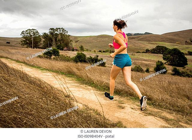 Female runner running on dirt track in landscape