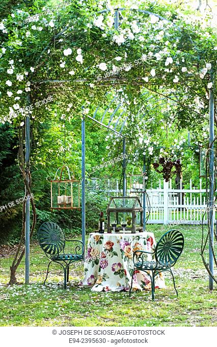 A table setting under a rose arbor with a fence in the background.Georgia USA