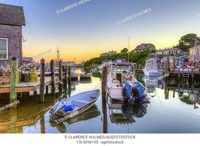 The commercial fishing village of Menemsha and boats docked in Menemsha Basin under a colorful sky during morning twilight, in Chilmark