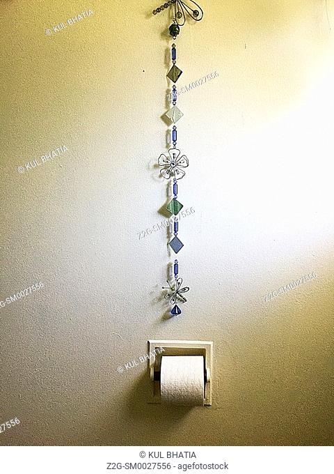 A chain of personal jewellery suspended over a roll of toilet paper. A simple decor in a contemporary bathroom, Ontario, Canada