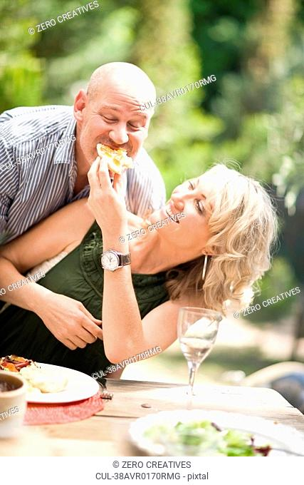 Woman feeding husband outdoors