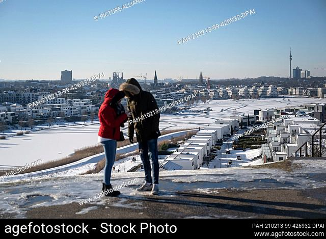 13 February 2021, North Rhine-Westphalia, Dortmund: Day trippers stand on the slag heap above the frozen Phoenix Lake and look out over the panorama of the city...
