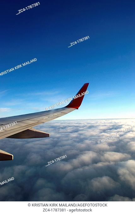 Looking out on wing af jetplane above the clouds
