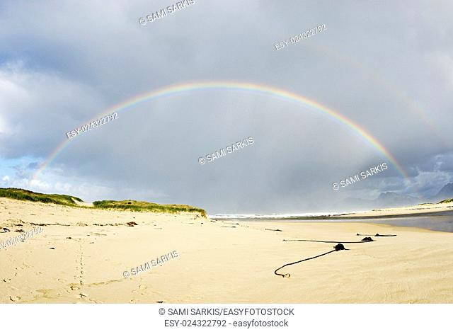 Beach and rainbow on a cloudy day, Hermanus, South Africa