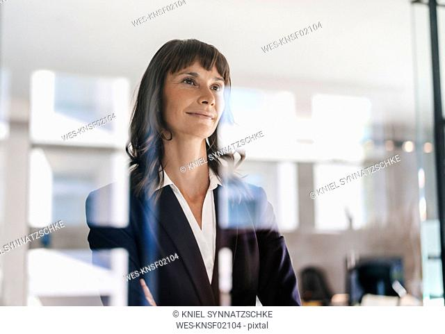 Successful businesswoman looking through glass pane