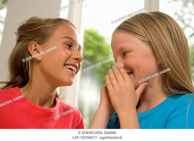 Girl whispering into girlfriend's ear, children's birthday party