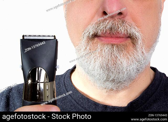 Gray-haired man holds an electric razor in his hand
