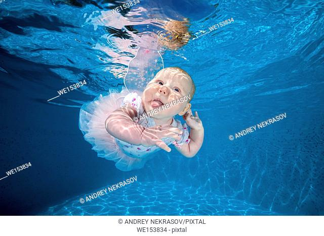 Little girl in fairy dress under water in the pool