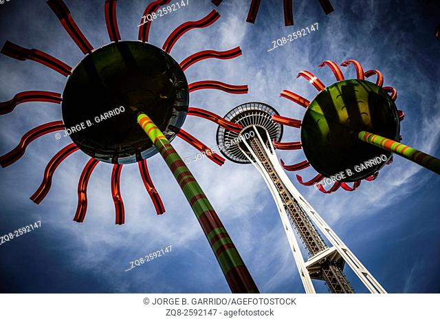 The landmark Space Needle soars overhead with two colorful flower sculptures
