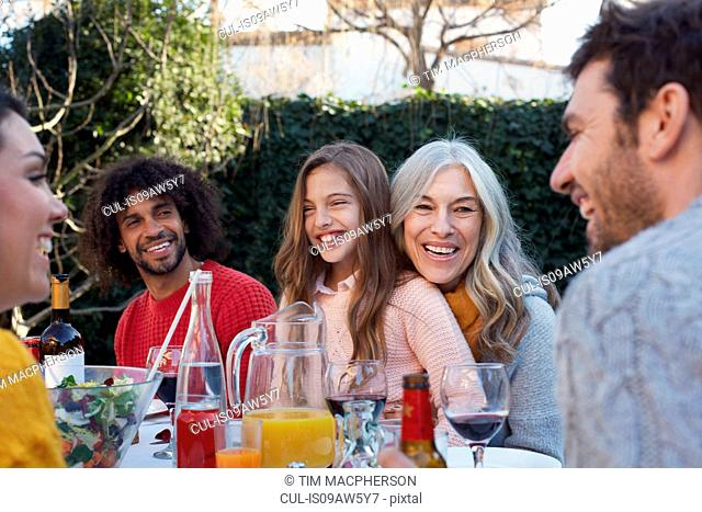 Multi generation family dining outdoors, smiling