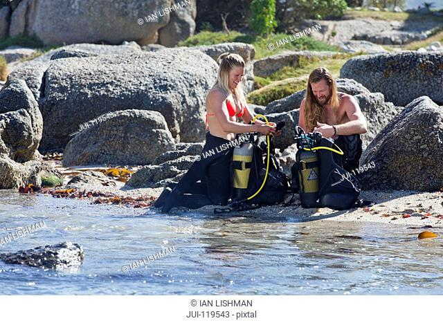 Couple preparing scuba equipment for a dive from the beach